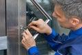 Male Lockpicker Fixing Door Ha...