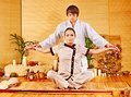 Male masseur doing massage woman in bamboo spa. Stock Photography
