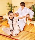 Male masseur doing massage woman in bamboo spa. Royalty Free Stock Images