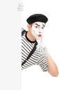 Male mime artist holding a blank panel and gesturing silence wit with finger on his mouth isolated on white background Royalty Free Stock Photo