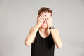 Male model covering eyes with hands fashion shot of thin young in studio Stock Photo