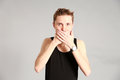 Male model covering mouth with hands fashion shot of thin young in studio Stock Photos