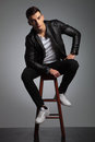 Male model in leather jacket posing seated while resting Royalty Free Stock Photo