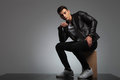 Male model in leather jacket posing seated while thinking Royalty Free Stock Photo