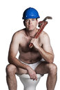 Male with naked torso bue helmet and wrench sitting on a toilet Stock Photography