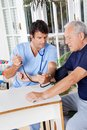 Male nurse checking blood pressure of a senior young patient at hospital Stock Images
