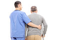 Male nurse helping an elderly gentleman isolated on white background rear view Stock Photography