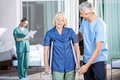 Male nurse helping senior woman to use crutches women with caretaker in background at nursing home Stock Photography
