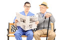 Male nurse reading newspaper to an elderly gentleman a seated on bench on white background Royalty Free Stock Photography