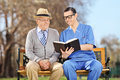 Male nurse reading to a pensioner in park shot with tilt and shift lens Royalty Free Stock Images
