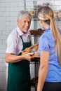 Male owner assisting female customer in buying senior muffins at supermarket Stock Photos
