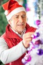 Male owner decorating christmas tree at store in santa hat Royalty Free Stock Photos