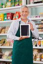 Male owner showing digital tablet in store portrait of happy senior supermarket Royalty Free Stock Photography