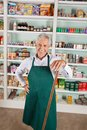 Male owner standing against shelves in supermarket portrait of happy senior Royalty Free Stock Images