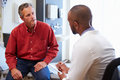 Male Patient And Doctor Have Consultation In Hospital Room Royalty Free Stock Photo