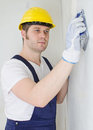 Male plasterer in hard hat polishing the wall Royalty Free Stock Photos