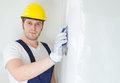 Male plasterer in hard hat polishing the wall space for text Stock Image