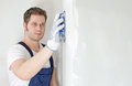 Male plasterer polishing the wall space for text Royalty Free Stock Images
