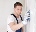 Male plasterer in uniform polishing the wall Stock Photography