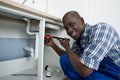 Male plumber fixing pipe of sink close up happy african in kitchen Stock Photography