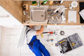Male Plumber In Overall Fixing Sink Pipe Royalty Free Stock Photo