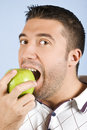 Male portrait taking a bite of an apple Royalty Free Stock Photo