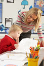 Male Primary School Pupil And Teacher Working Stock Photos