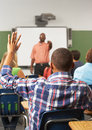 Male pupil raising hand in class answering question sitting down Royalty Free Stock Photos