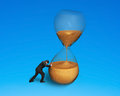 Male pushing tilt hourglass isolated on blue Royalty Free Stock Images