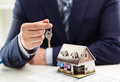 Male realtor selling house or apartment giving a key to client with building model at table shallow depth of field Stock Image