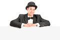 A male with retro hat and bow tie posing behind a blank panel isolated on white background Royalty Free Stock Image