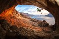 Male rock climber climbing along a roof in a cave at sunset Royalty Free Stock Photos