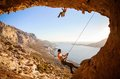 Male rock climber climbing on a roof in a cave his partner belaying Royalty Free Stock Photos