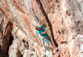Male Rock Climber on high orange natural stone Wall Royalty Free Stock Photo