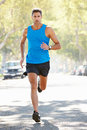 Male runner exercising on suburban street running towards camera Stock Photography