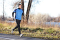 Male runner man running in autumn on cold day wearing long tights and long sporty jogging outfit fit fitness athlete model Royalty Free Stock Photo