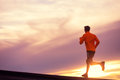 Male runner silhouette, running into sunset Royalty Free Stock Photo