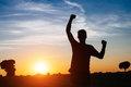 Male runner success and win successful man raising arms after cross country running on summer at sunset athlete with arms up Stock Photo