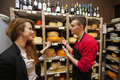 Male salesperson showing cheese to female customer in store Royalty Free Stock Photo