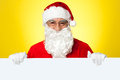 Male Santa standing behind big blank banner Stock Photo