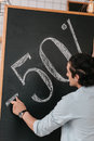 Male seller drawing fifty percent discount sign on chalkboard Royalty Free Stock Photo