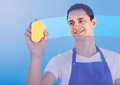 Male servant cleaning glass with sponge portrait of young over blue background Stock Photos