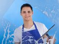 Male servant cleaning glass with squeegee Royalty Free Stock Photo