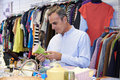 Male shopper in thrift store looking at ornaments shopping Royalty Free Stock Photo