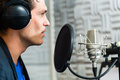 Male singer or musician for recording in studio young with microphone and headphone audio the Royalty Free Stock Photos