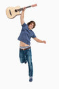 Male student jumping with his guitar Stock Images