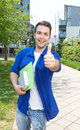 Male student with paperwork on campus showing thumb up university building in the background Royalty Free Stock Images