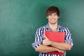 Male student with red binder standing against chalkboard portrait of handsome young Royalty Free Stock Image