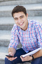 Male student smiling with mobile phone and notebook Stock Photo