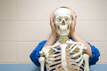 Male student stood behind human skeleton Royalty Free Stock Photo